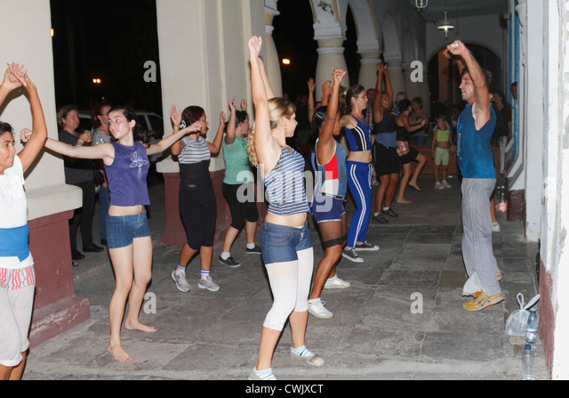 Cuban teenagers, youth, dancing on the street night time. Cienfuegos, Cuba, November 2010 - Stock Image