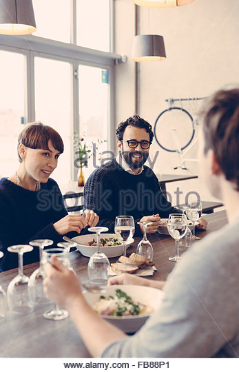 Sweden, Friends talking at restaurant - Stock Image