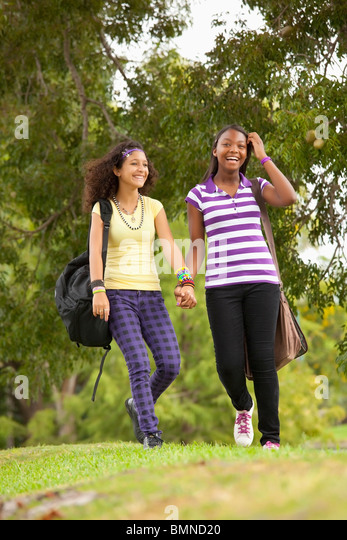 Fort Lauderdale, Florida, United States Of America; Two Teenage Girls Walking Through A Park With Their School Bags - Stock Image