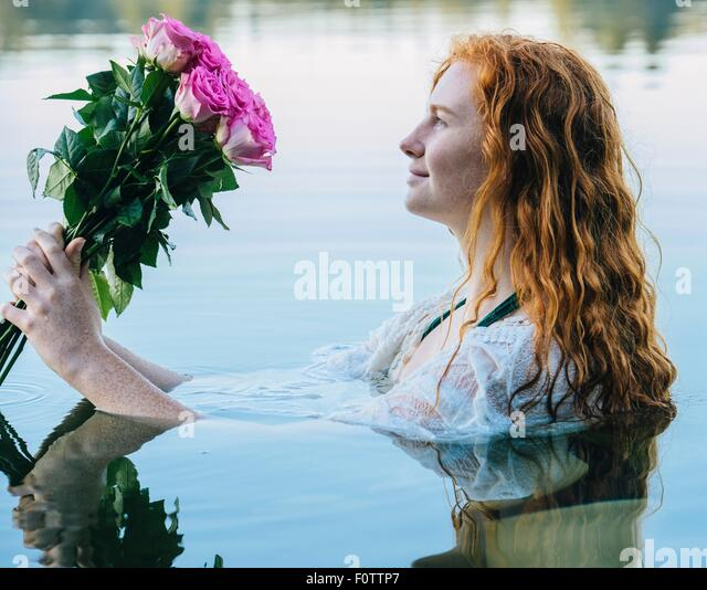 Head and shoulders of young woman with long red hair in lake gazing at bunch of pink roses - Stock-Bilder