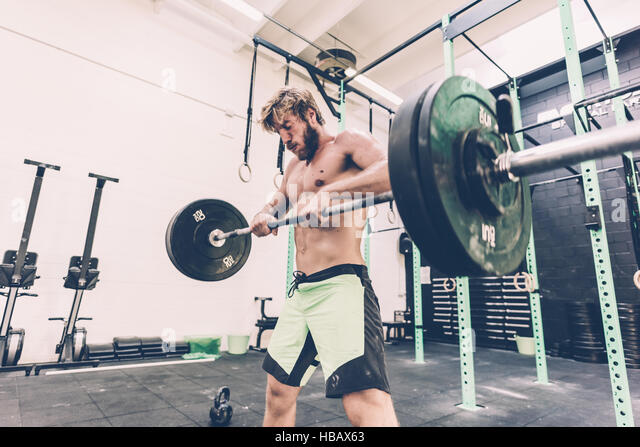 Young man weightlifting barbell in cross training gym - Stock Image