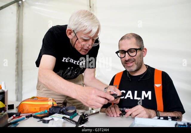 Restart project . A man wearing a t shirt saying 'calm' fixes a broken dvd player, - Stock Image