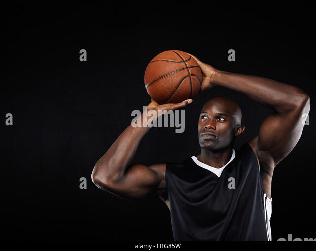 Young African American male basketball player shooting at the hoop against black background - Stock Image