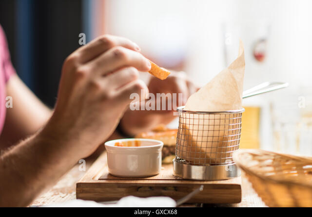 Hand of young man eating chips in restaurant - Stock Image