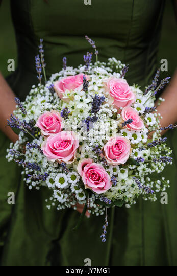 Wedding bouquet on a green dress background - Stock Image