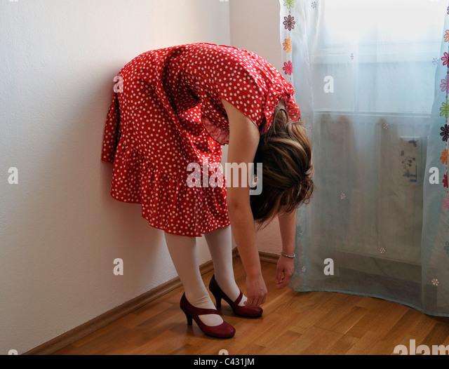 Young woman wearing polka dot dress bending over - Stock Image