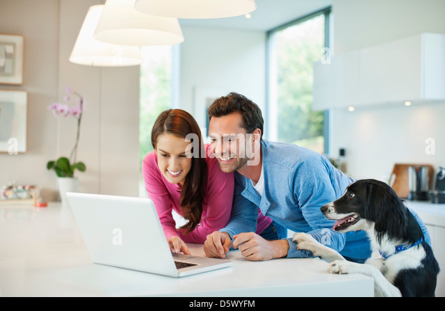 Couple using laptop with dog at table - Stock Image