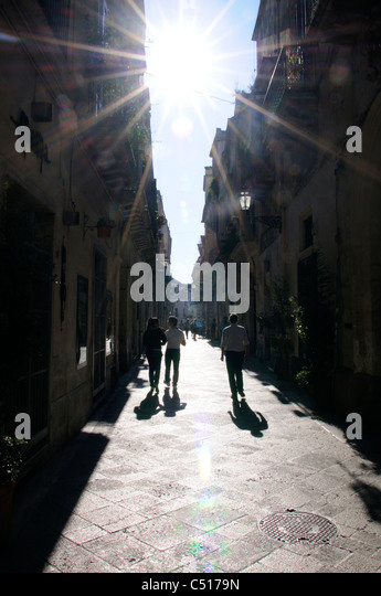 Silhouetted tourists walking in street, Lecce, Puglia, Italy - Stock Image