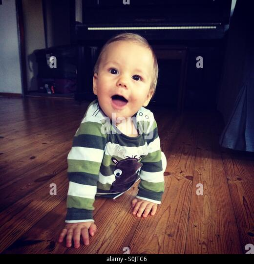 Happy baby boy learning how to crawl on a wooden floor, indoors  in the living room of a Polish  apartment - Stock Image