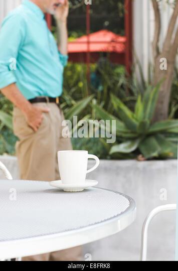 Businessman at cafe taking call - Stock-Bilder