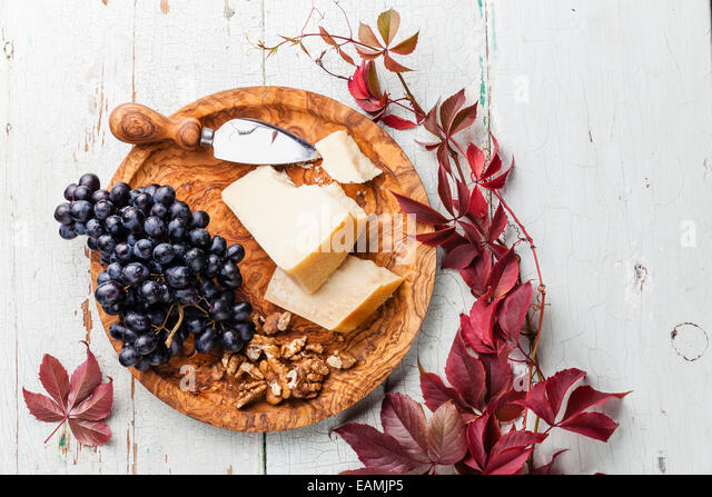 Parmesan cheese, grapes and walnut on olive wood plate - Stock Image