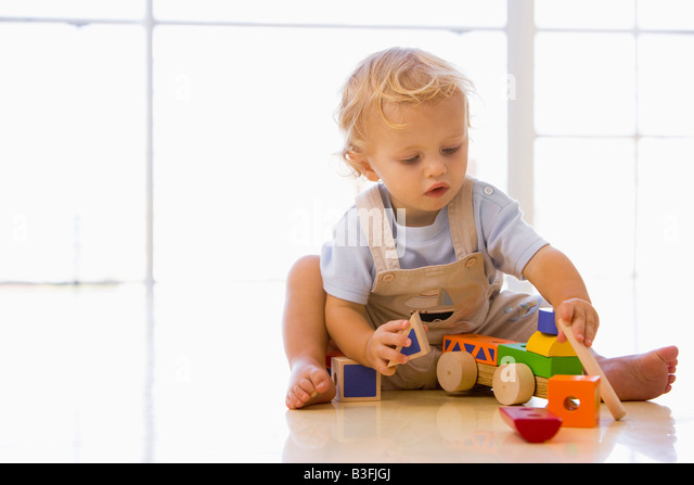Baby indoors playing with toy truck - Stock Image