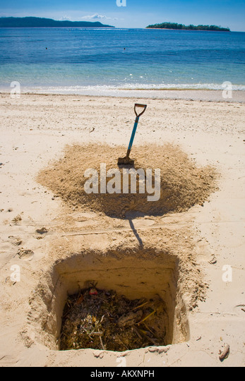 Garbage will bury in a pit on the beach. Indonesia. - Stock Image