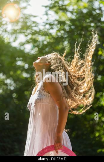 Teenage girl wearing white sundress tossing long hair, Prague, Czech Republic - Stock Image