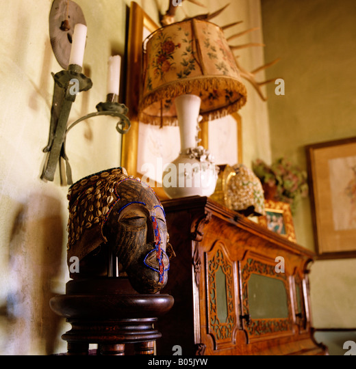 corner of a room with tribal mask and old fashioned lamp on console - Stock-Bilder