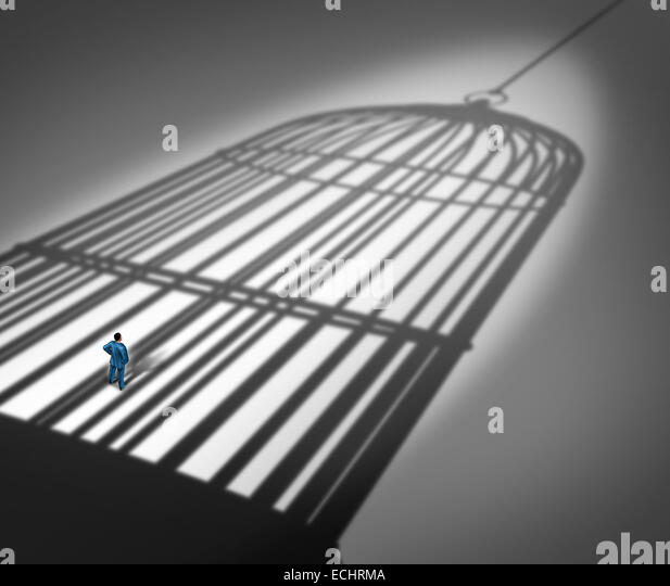 Feeling trapped in a prison concept as a person standing inside the cast shadow of a giant bird cage as a metaphor - Stock Image