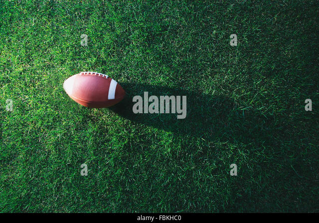 American football ball on grass - Stock Image