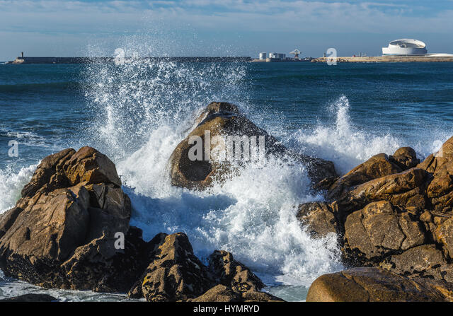 Waves smashing against rocks on the beach in Nevogilde civil parish of Porto, Portugal. Port of Leixoes Cruise Terminal - Stock Image
