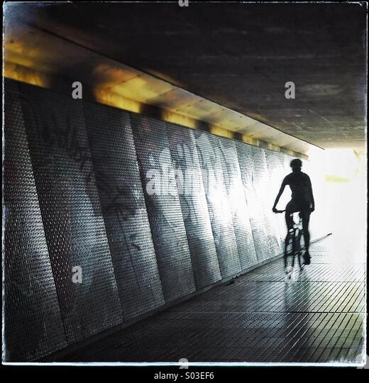 Silhouette of a bycicle through a dark underpass symbolizing light at the end of the tunnel - Stock Image