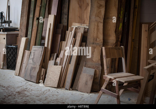 Detail of a furniture makers workshop showing wood stacked and an unfinished chair - Stock-Bilder
