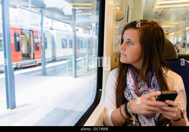 Young female tourist on local train, Catalonia, Spain - Stock-Bilder