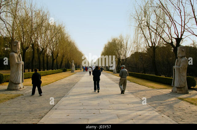 Visitors walk along the Sacred Way near the Ming Tombs. Beijing, China. Late afternoon on an early spring day with - Stock Image