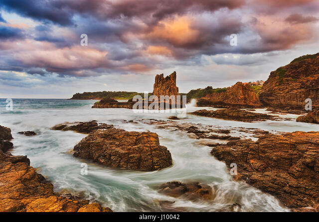 Colourful sunset at Bombo beach and Cathedral rocks in Kiama, Pacific coast of Australia. Eroded sandstone rocks - Stock Image