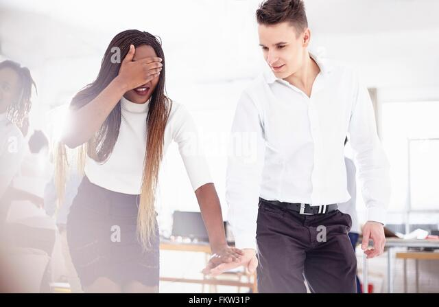 Colleagues in team building task, hand covering eyes, holding hands - Stock Image