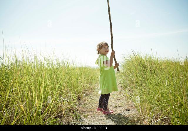 Portrait of female toddler holding long stick - Stock Image