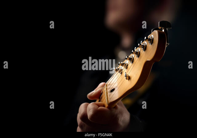 Guitarist on stage - closeup with selective focus on guitar head - Stock Image