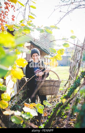 View through leaves of young woman in garden wearing knit hat holding wickerwork basket looking at camera smiling - Stock Image