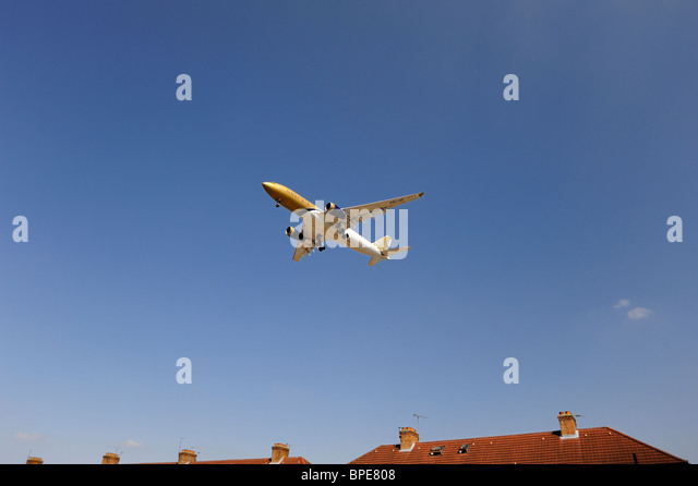 Gulf Air aeroplane flying low over house prior to landing - Stock Image