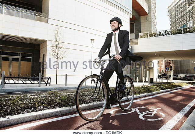 Mid adult businessman riding bike on cycle path - Stock Image