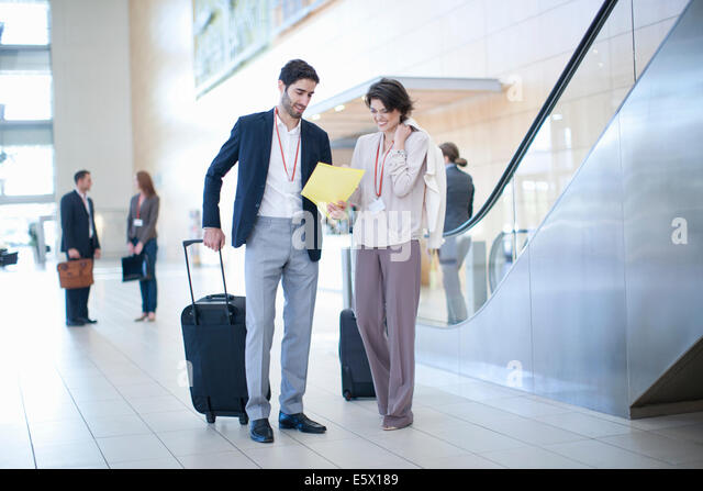 Businessman and businesswoman arriving in conference centre atrium - Stock Image
