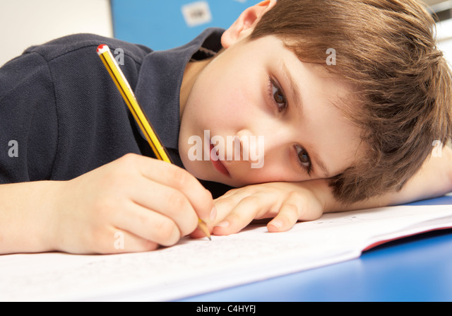 Unhappy Schoolboy Studying In Classroom - Stock Image