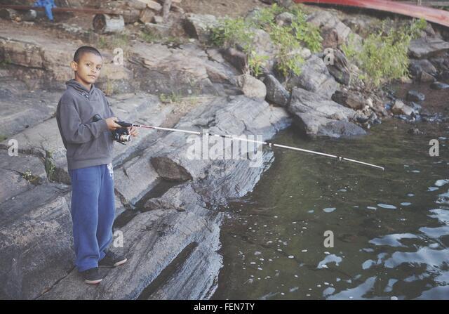 Boy Fishing At Riverbank - Stock Image
