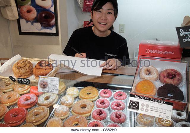 Tokyo Japan Ikebukuro JR Ikebukuro Station Doughnut Plant donut bakery shop Asian woman manager employee bookkeeping - Stock Image