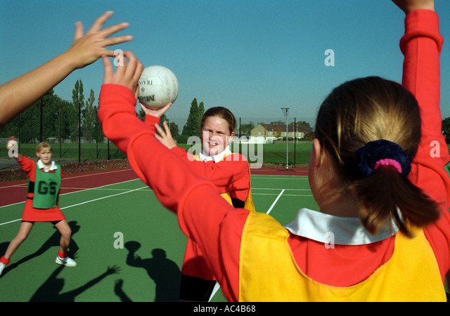 Females playinGBasket netball at a secondary school - Stock Image