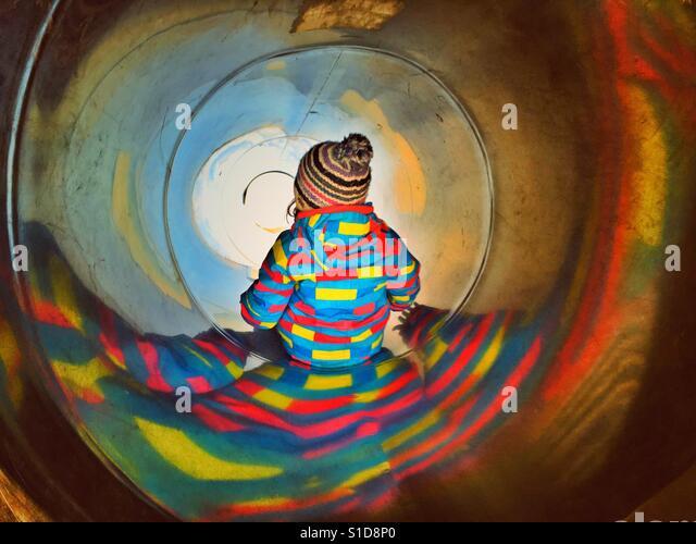 Child in sliding tube - Stock-Bilder