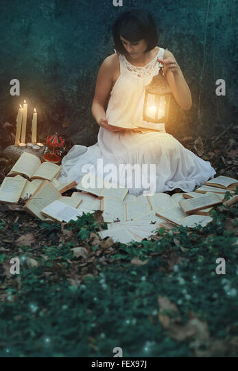 Beautiful woman reading books in the dark forest. Surreal and weird - Stock-Bilder