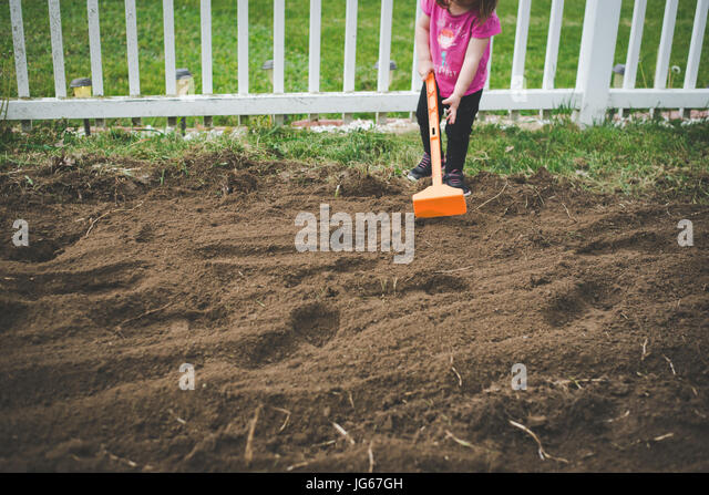 A toddler helps to hoe a garden in a backyard. - Stock Image