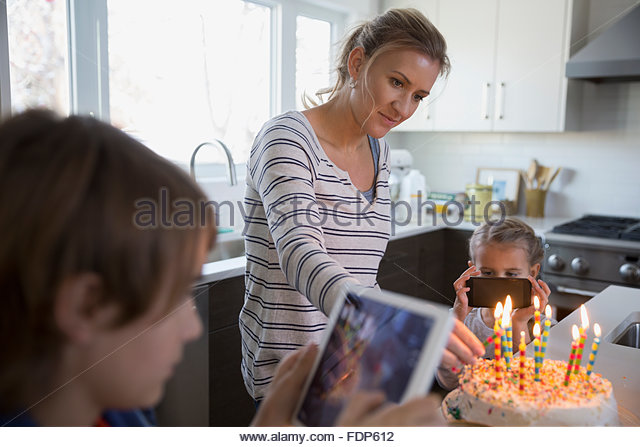 Mother and children photographing birthday cake with candles - Stock Image