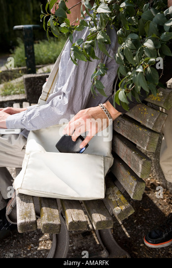 A thief stealing a purse from a handbag - Stock Image