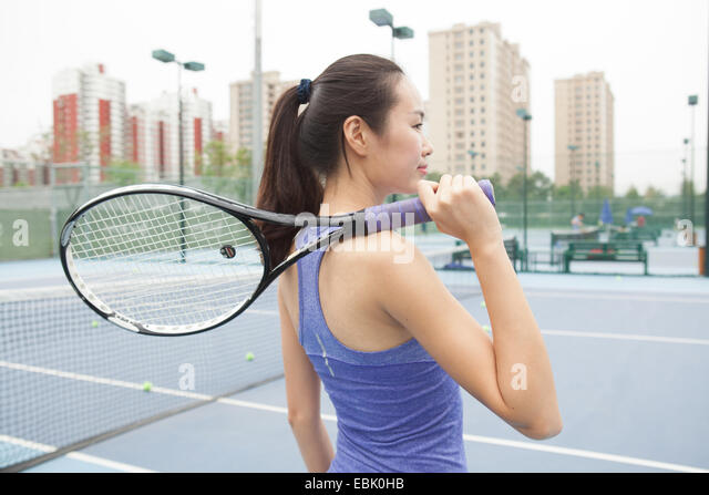 Young female tennis player with tennis racket on shoulder on tennis court - Stock Image