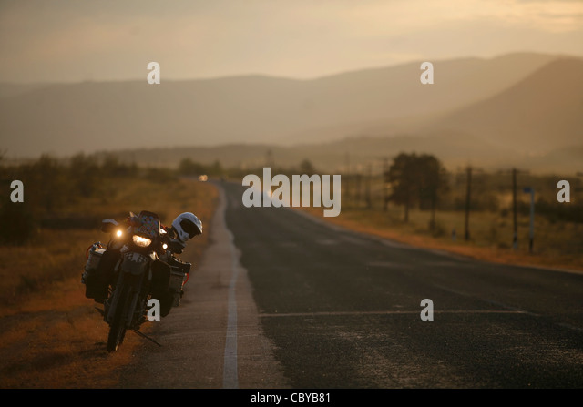 Motorcycle on a straight road at dusk - Stock Image