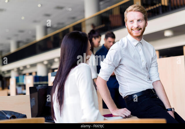 A group of academics studying in the library and conversing in a positive mood - Stock Image
