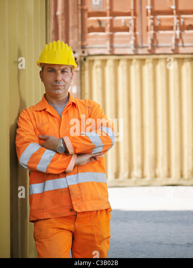 portrait of mid adult worker leaning on cargo container and looking at camera. Vertical shape, front view, copy - Stock Image