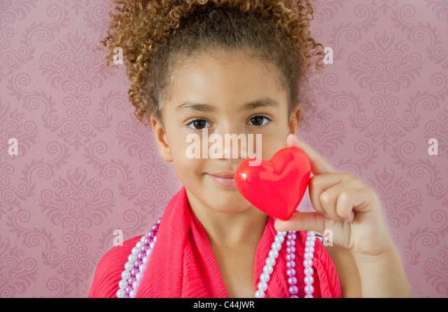 young girl holding a heart in a pink room - Stock Image