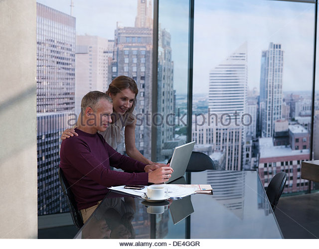 Couple working on computer with cityscape in background - Stock-Bilder