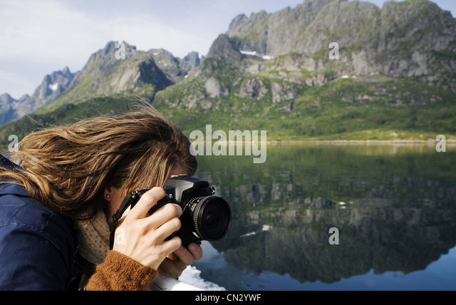 Woman taking a photograph in mountain landscape - Stock Image